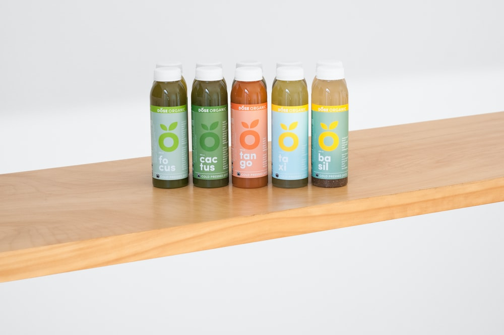 five glass bottles on brown wooden table
