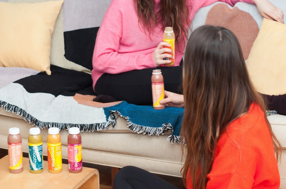 woman wearing orange shirt near woman sitting on sofa