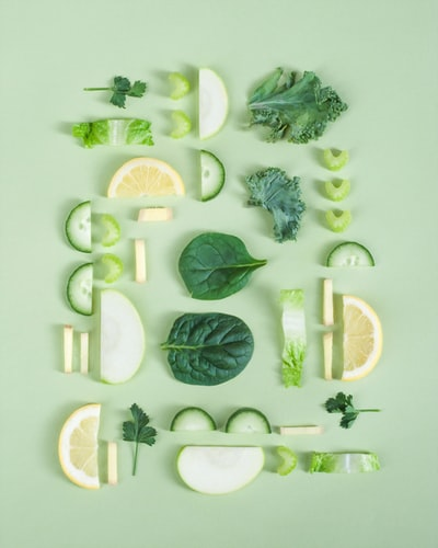 Green fruits and vegetables are cut and arranged on a green background