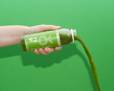 A bottle of green DOSE Juice pours out against a green background