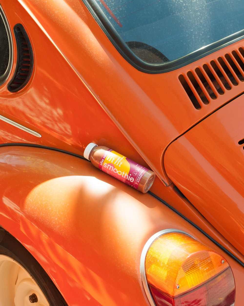 A bottle of DOSE Juice smoothie lies on an orange car