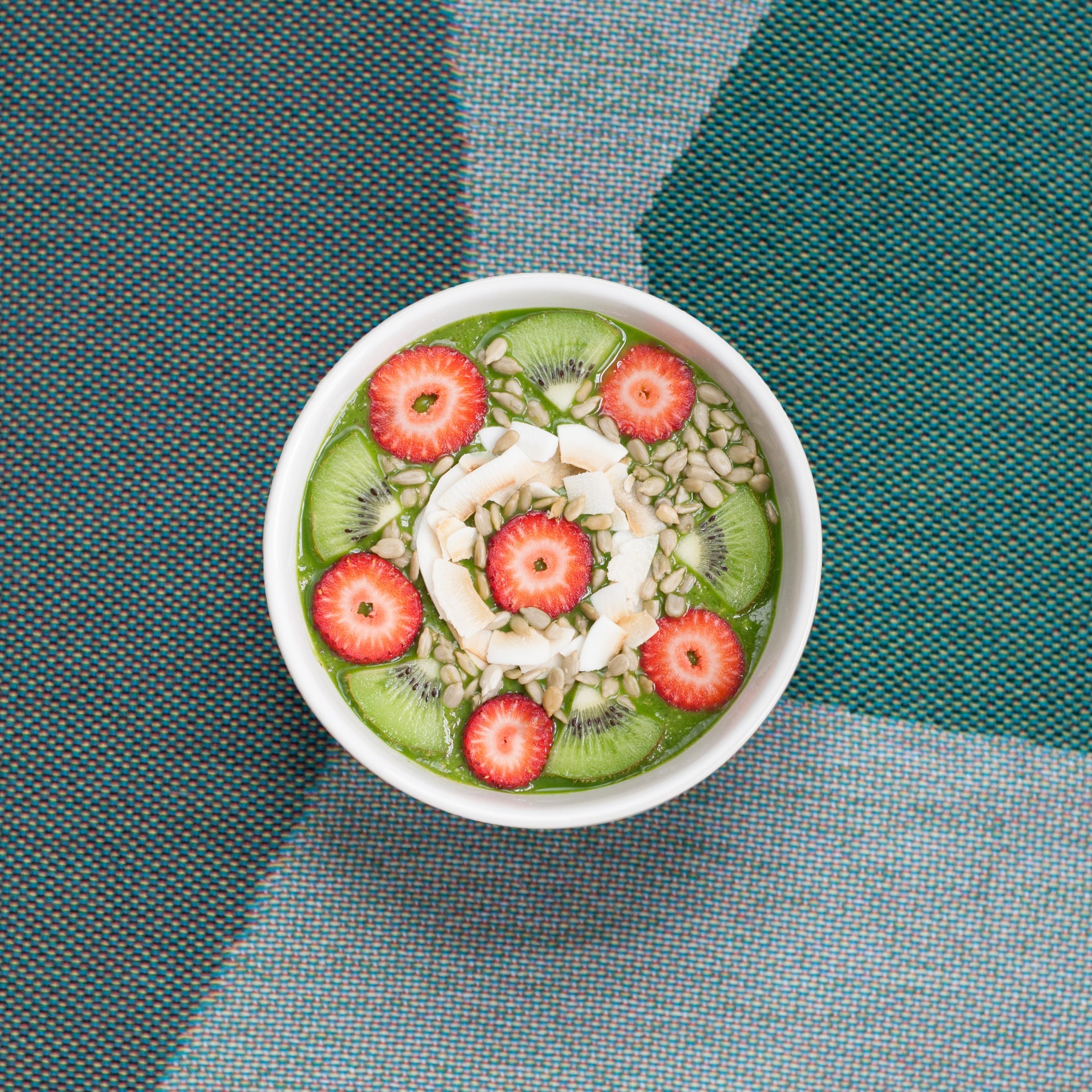 A bowl of kiwi, strawberries, and granola