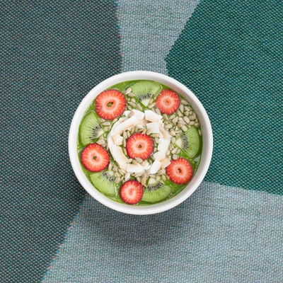 A bowl of kiwi, strawberries, and granola