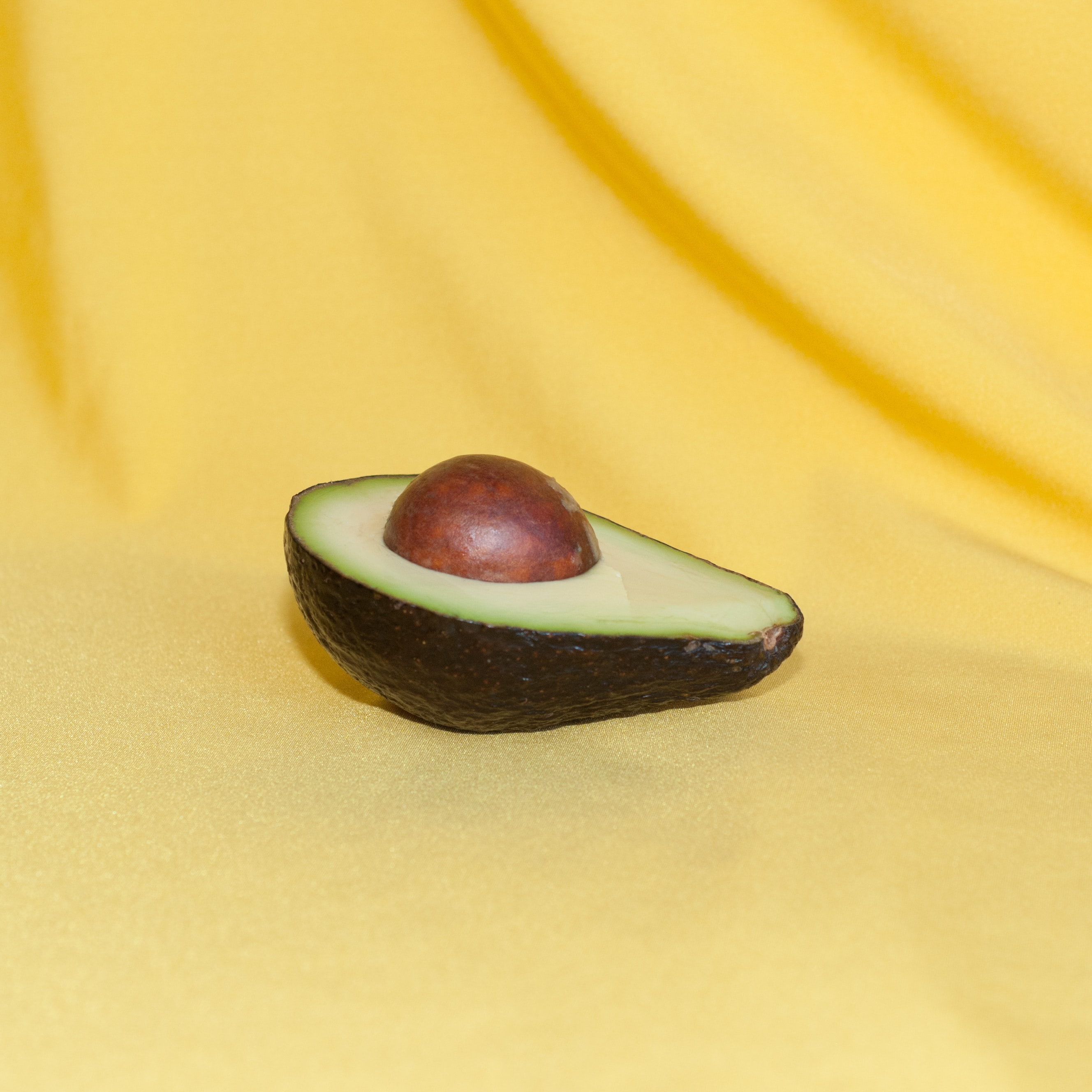 Half of an avocado against a yellow background