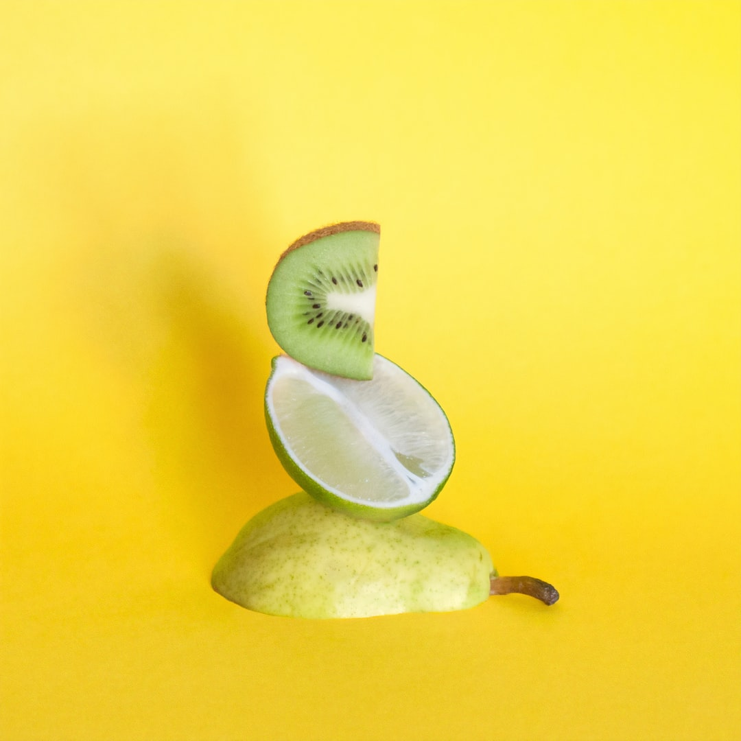 A pear, a lime, and a kiwi balance on a yellow background