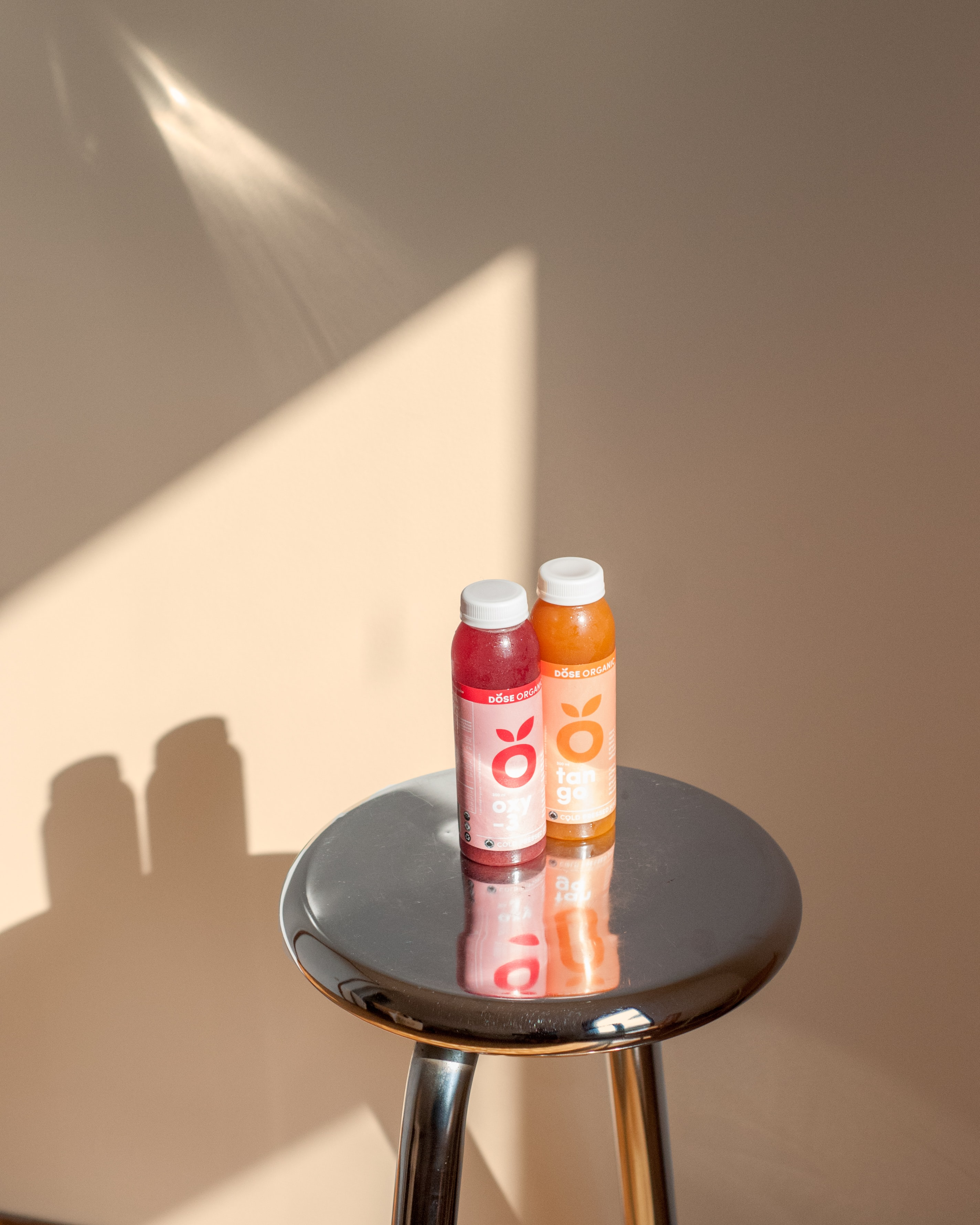 Two bottles of DOSE Juice on a stool