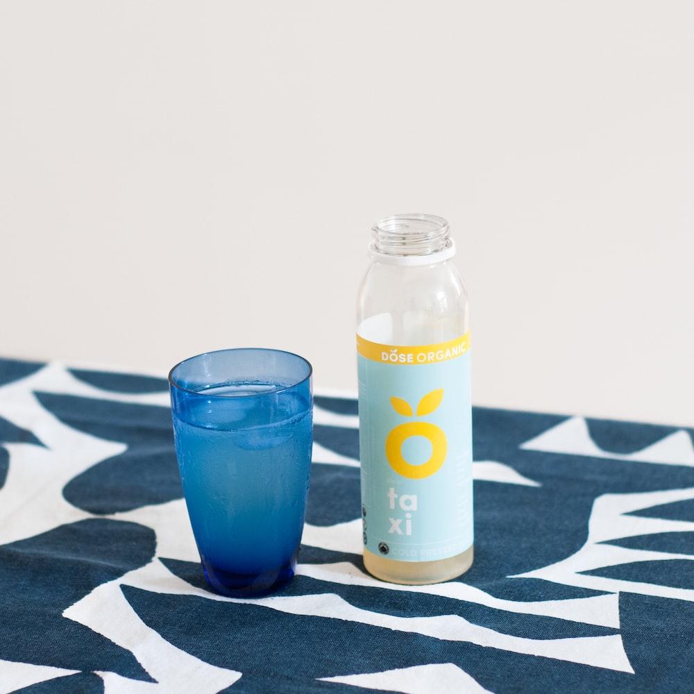blue drinking glass near plastic bottle