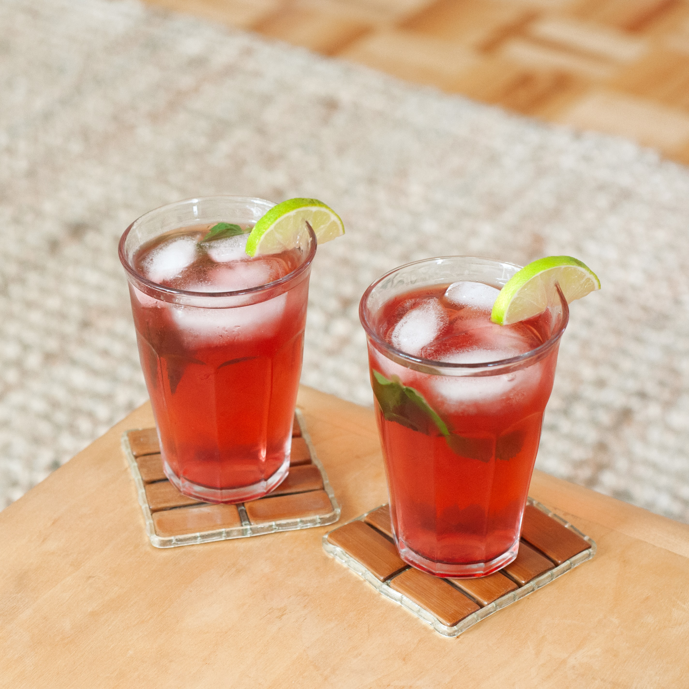 Two glasses with red DOSE Juice, ice, and a slice of lime