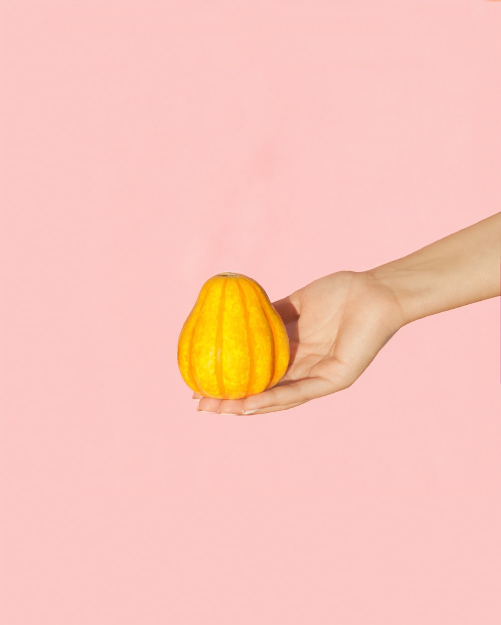 pear-shaped yellow fruit on person's palm