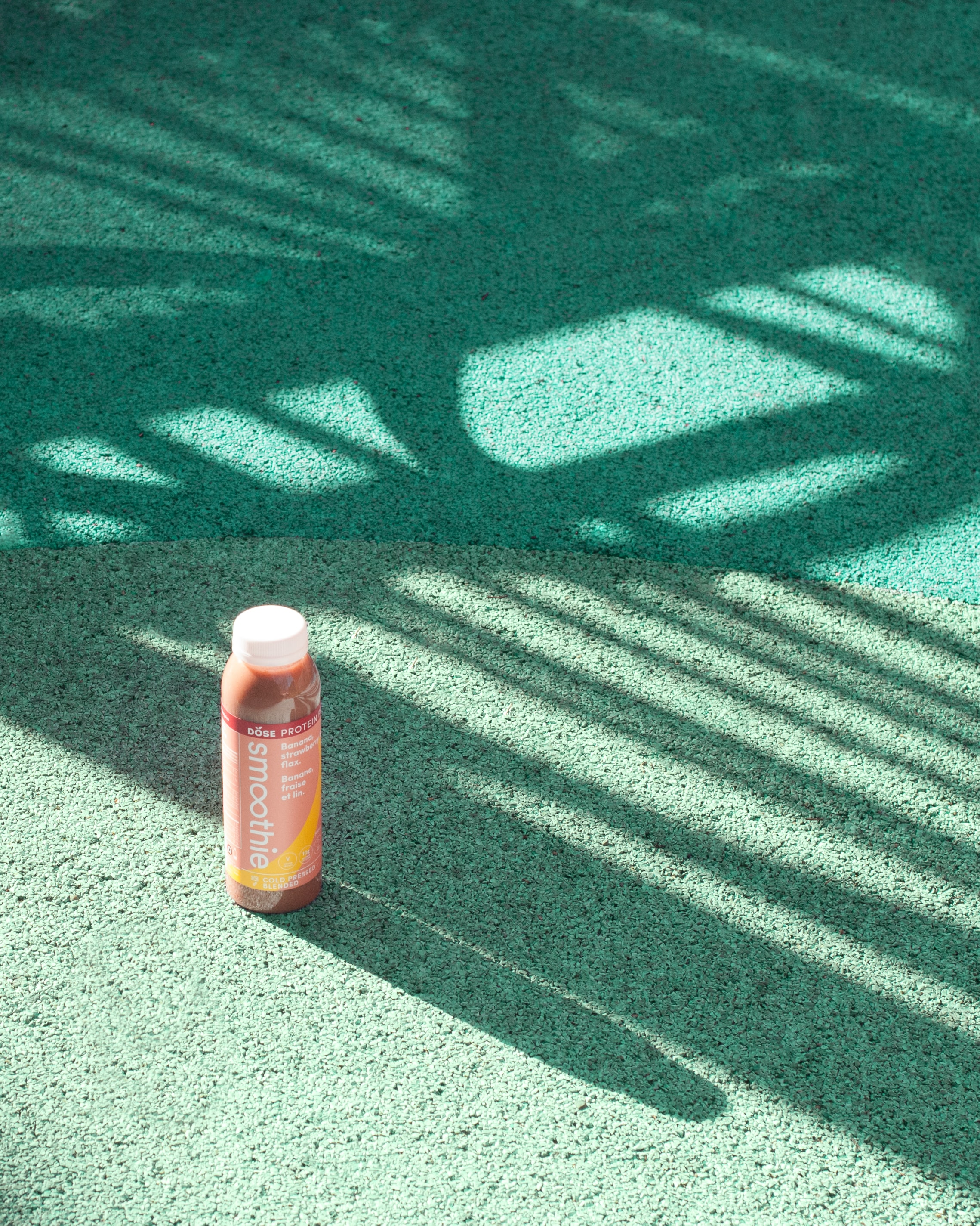 A bottle of DOSE Juice in the shadows