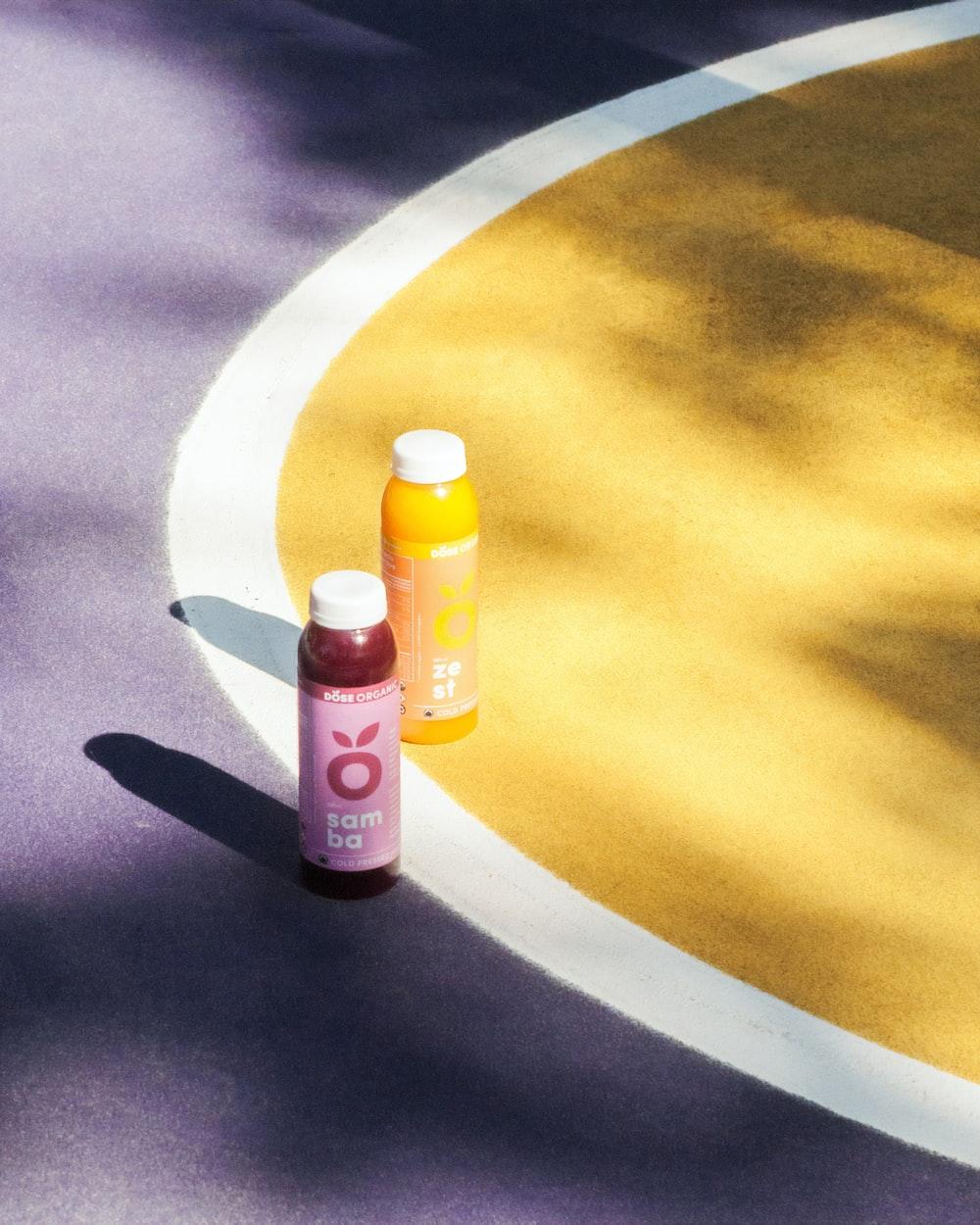 two fruit juice bottles on ground