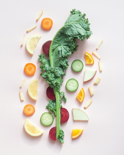 Slices of fruit and a stalk of kale on a pink background
