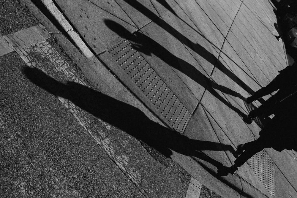 grayscale photo of person walking on roadway