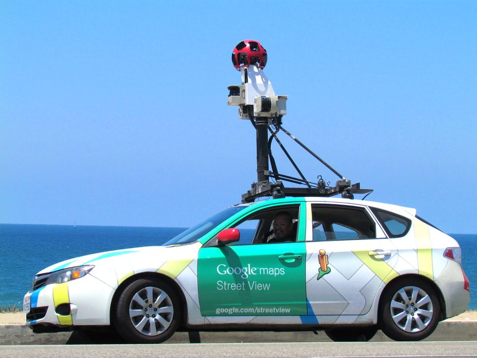 A man driving that works for Alphabet (Google), drives a car and takes imagery for Google Maps.