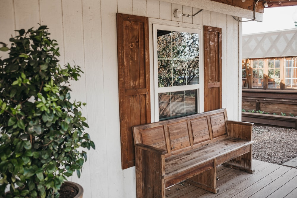 brown wooden bench beside white wooden wall