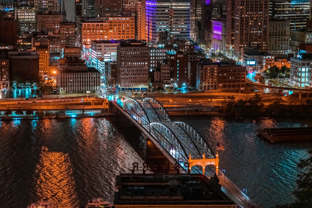 aerial photography of bridge and buildings at night time