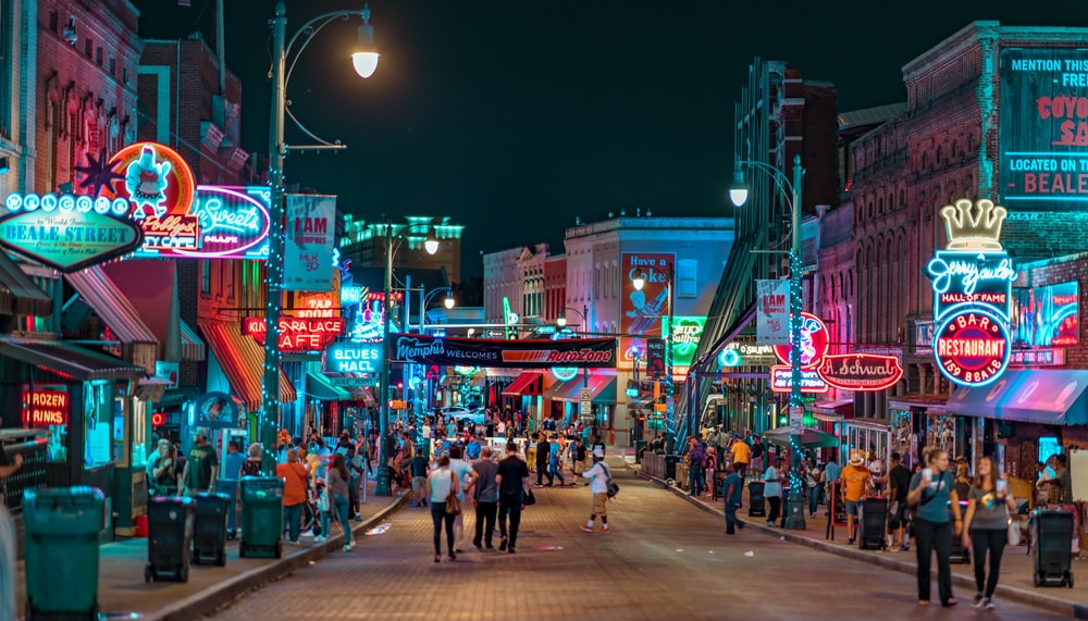people walking in middle of road in between establishments at night time
