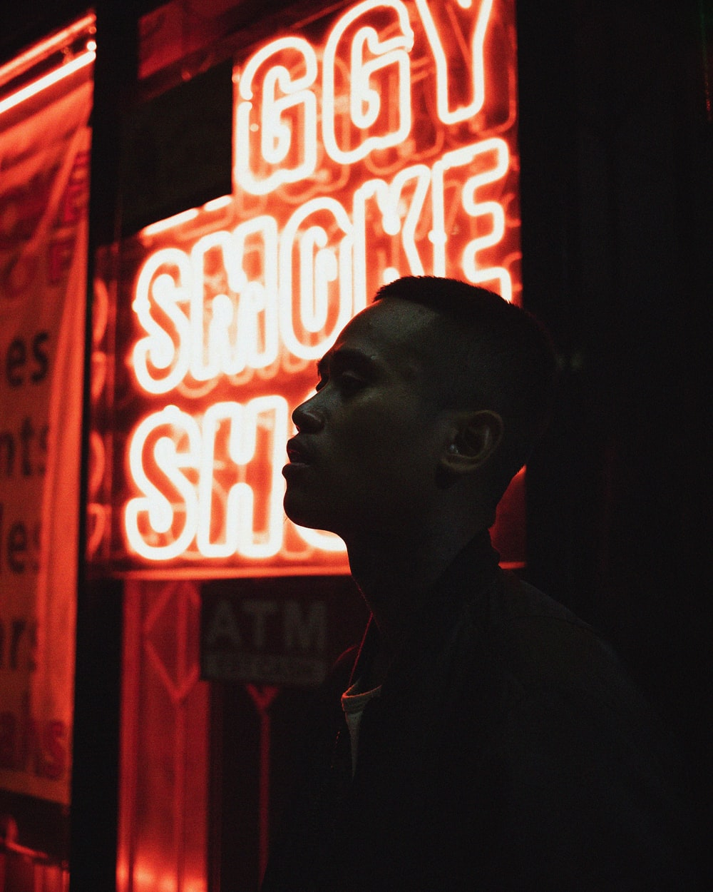 man standing beside neon light
