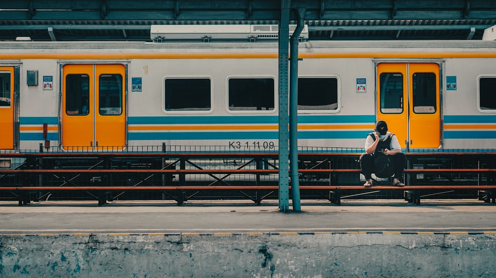 person sitting on bench near train