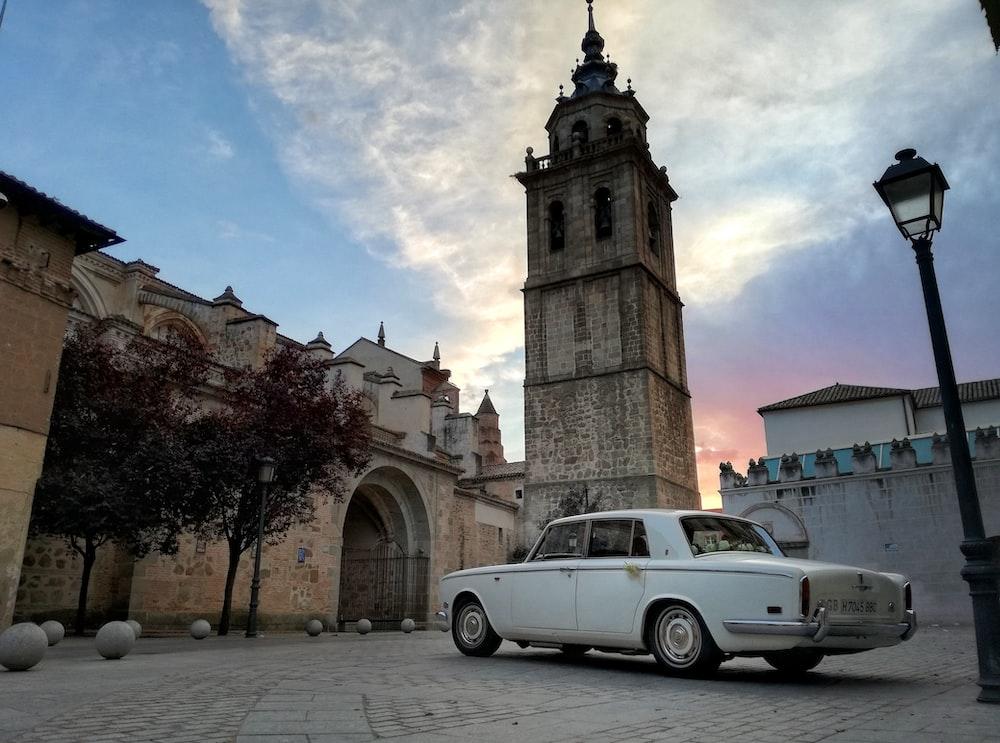 white sedan near brown concrete church