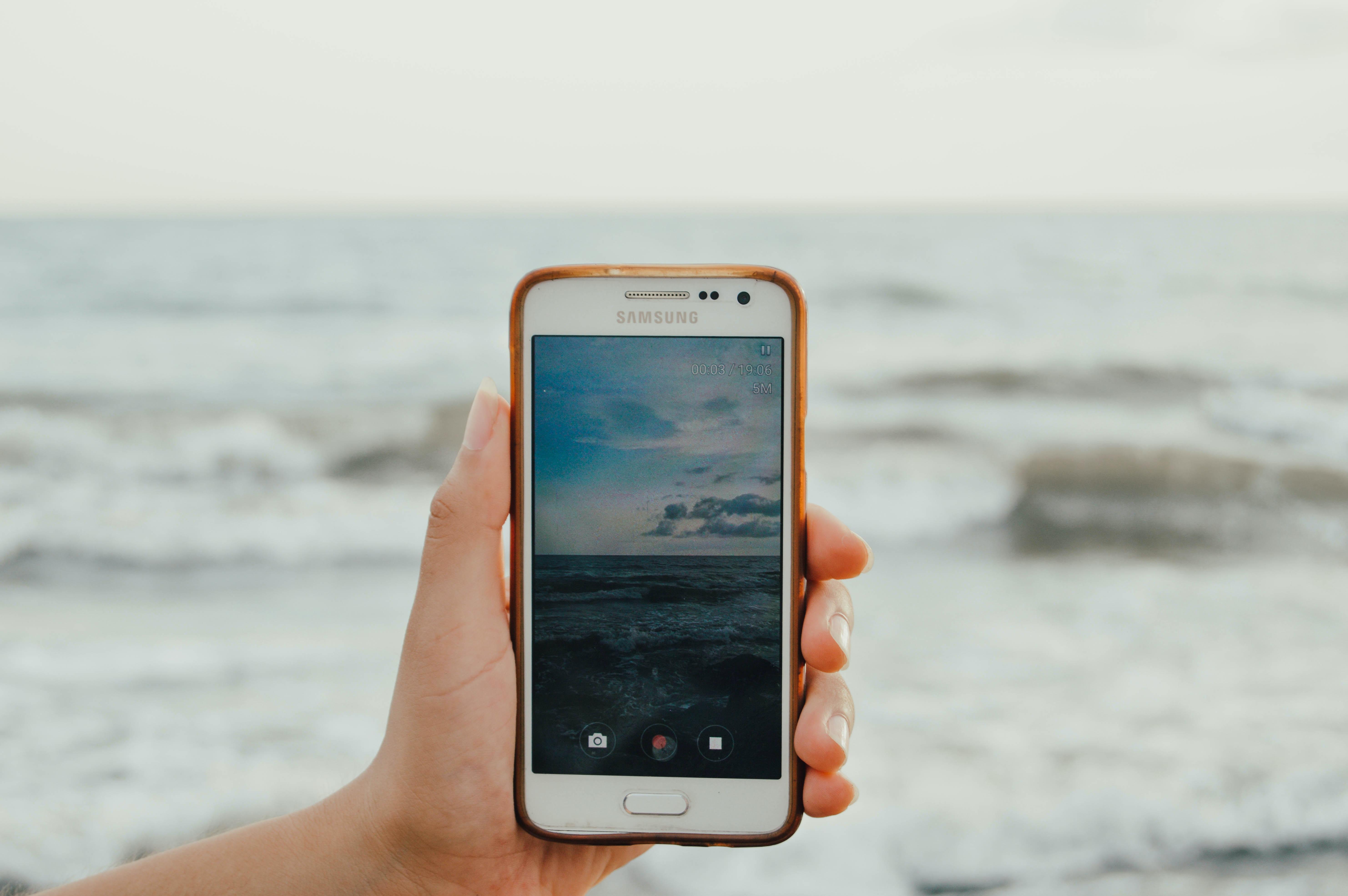 white Samsung Galaxy smartphone with orange case