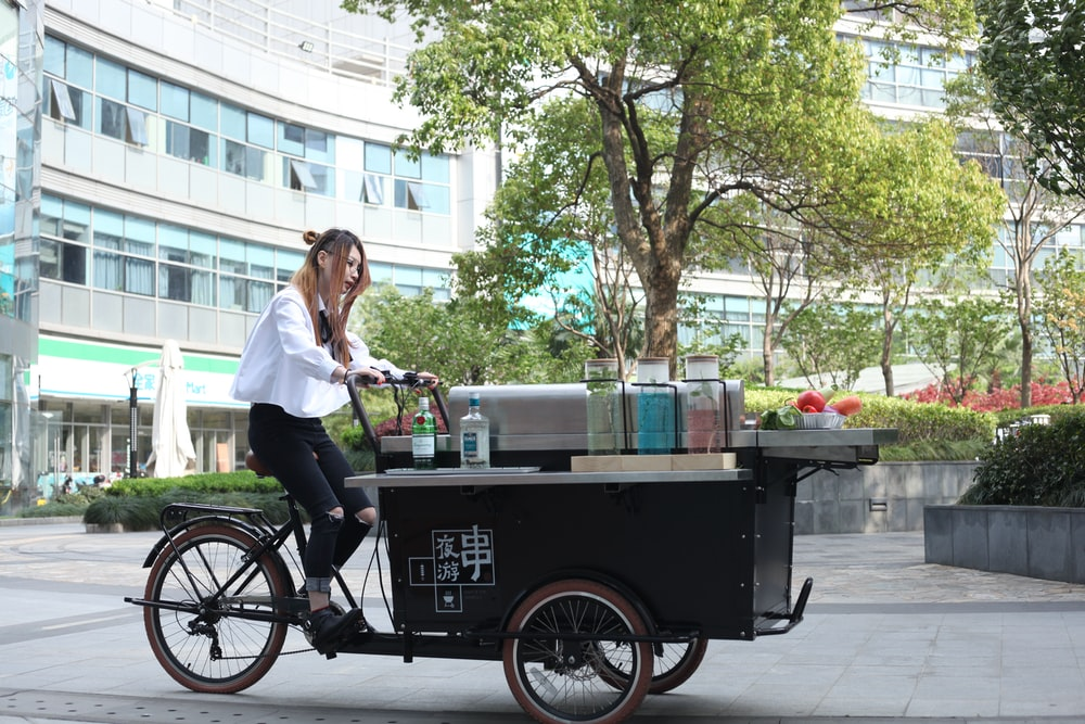woman riding on black food cart near concrete building