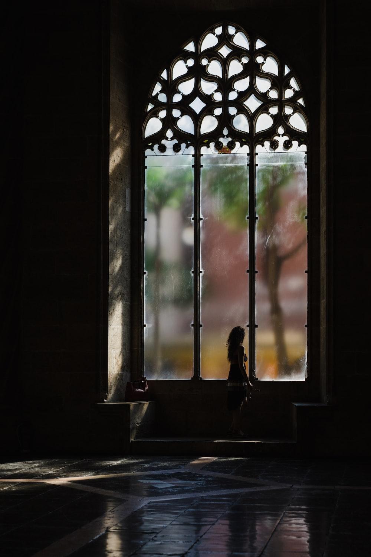 person standing beside framed glass window