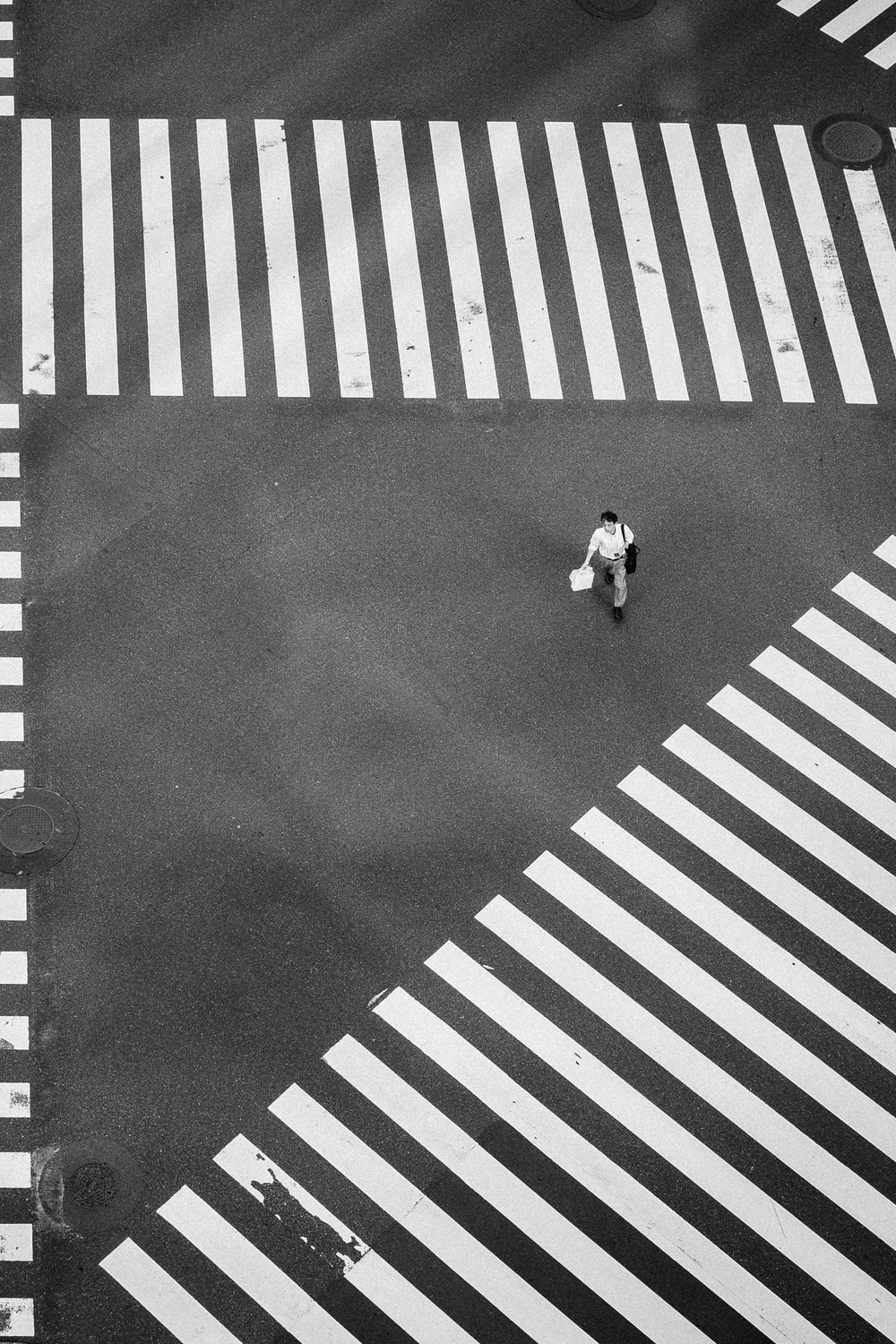 man walking at the center of crisscrossing pedestrian lanes