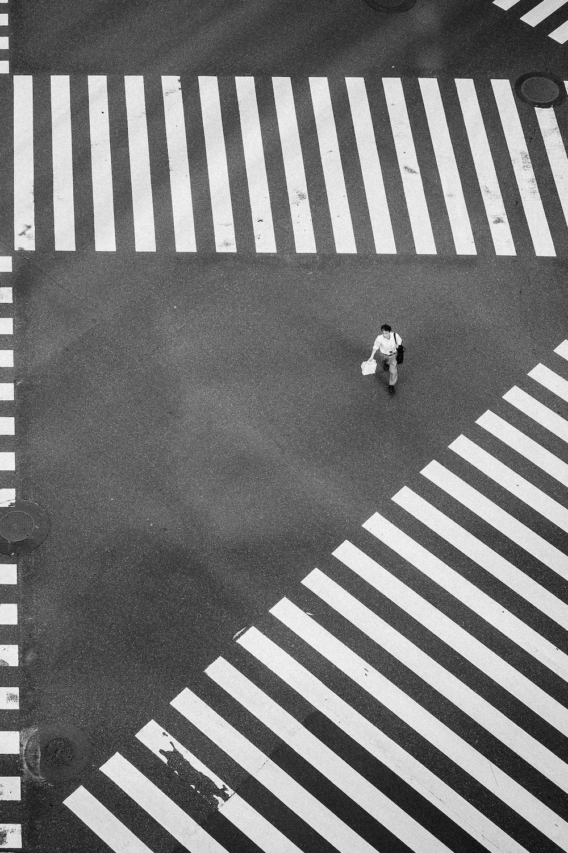 man walking at the center of crisscrossing pedestrian lanes