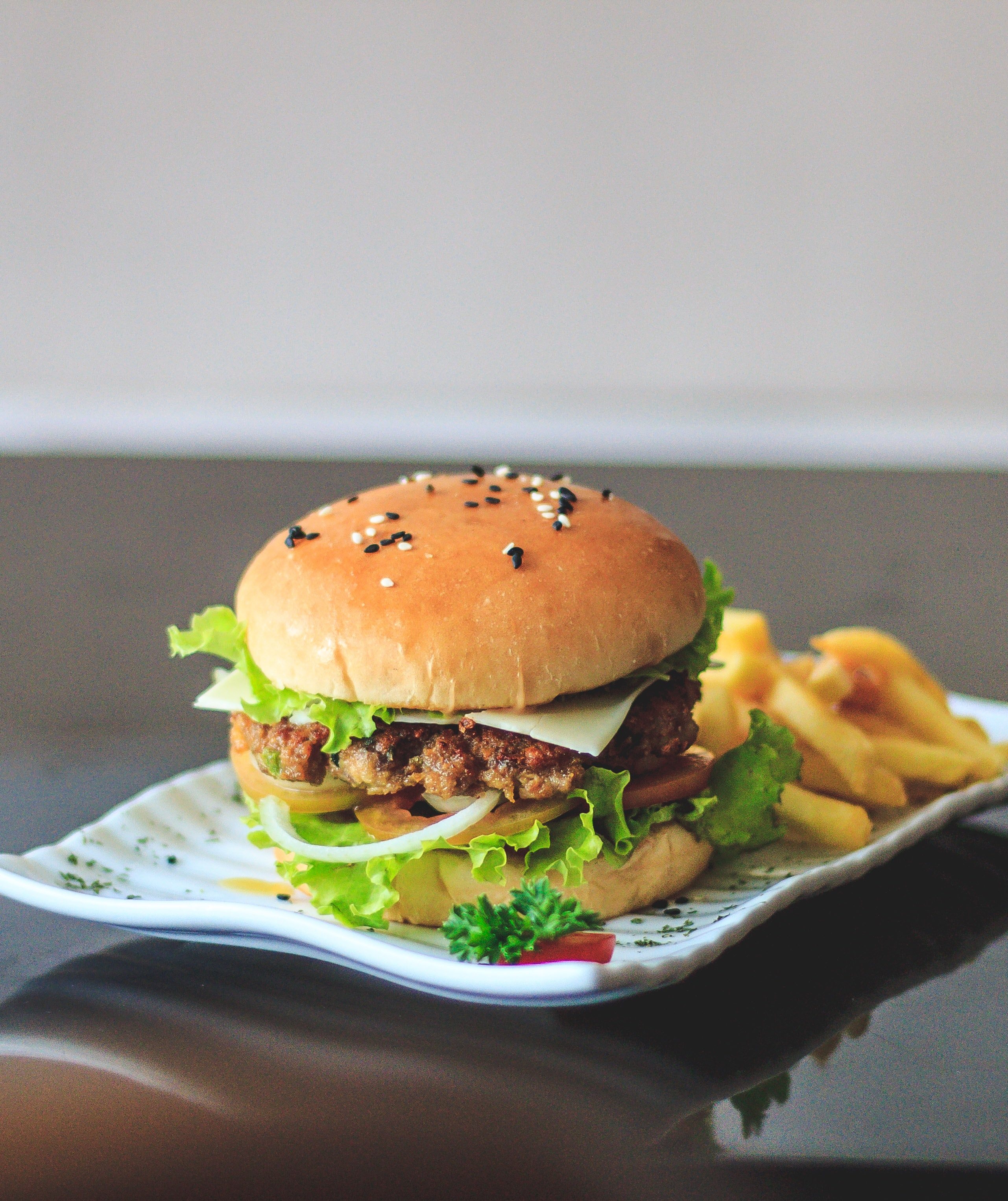 hamburger with lettuce and fries on white ceramic plate