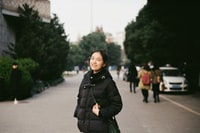 selective focus photography of woman standing on road