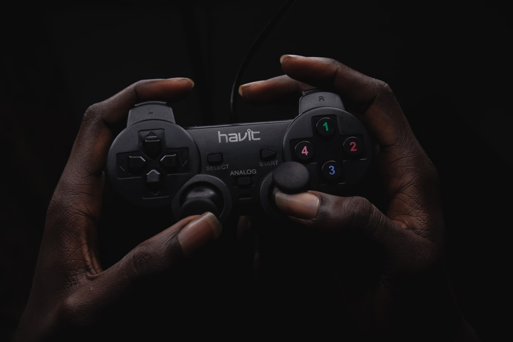 person holding black Havit game controller