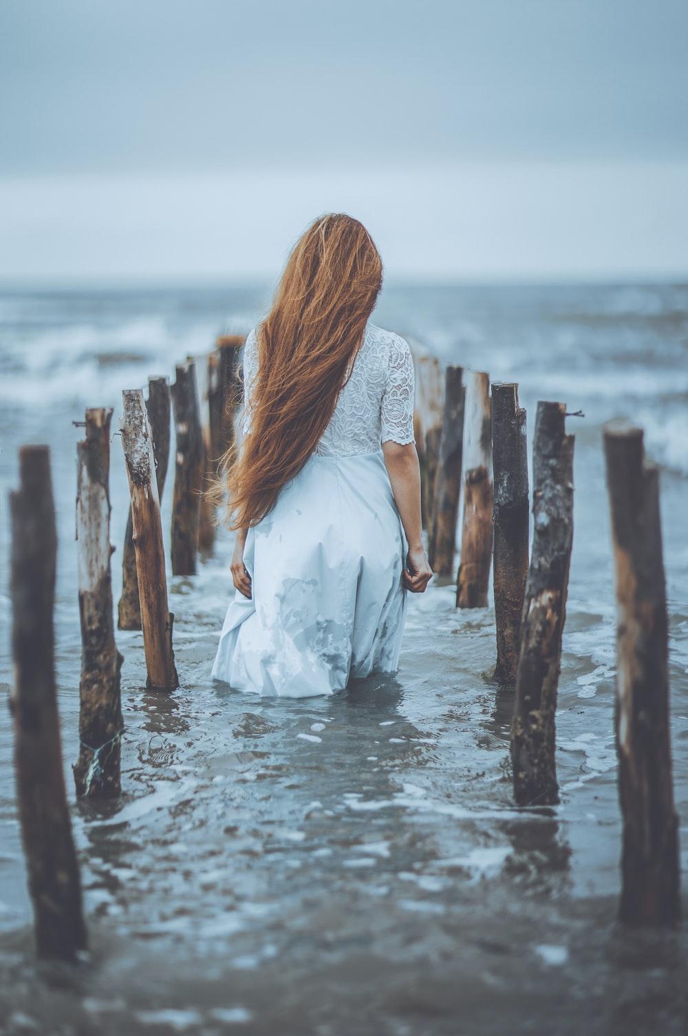 woman standing on water in between logs