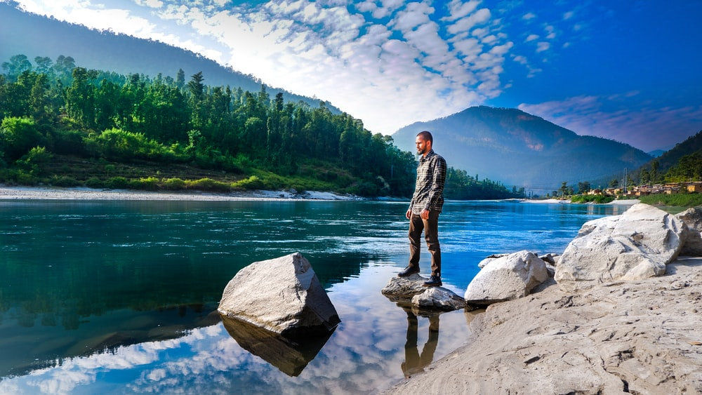 man standing on rocks above body of water overlooking mountains at daytime