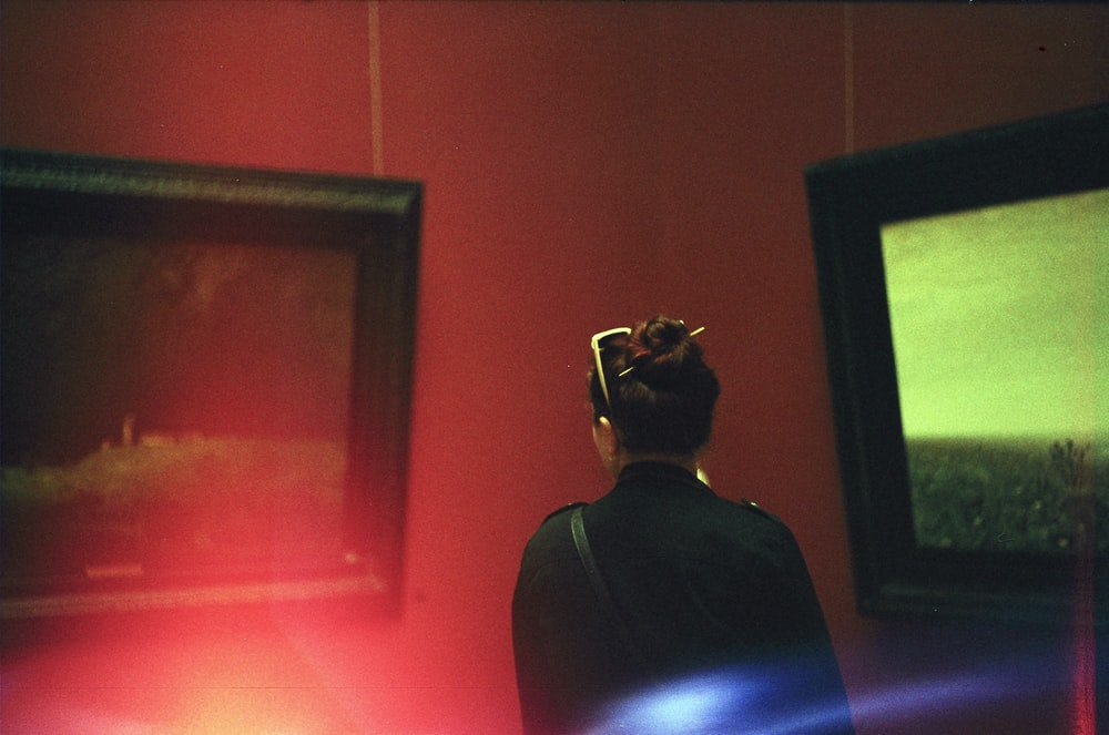 woman standing facing two black wooden framed paintings inside room