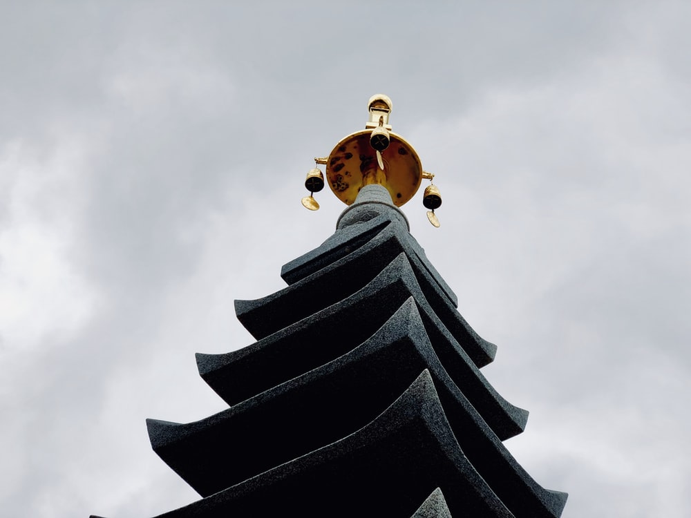 temple with gold tower under gray sky