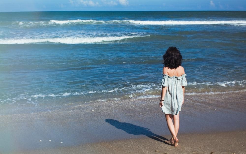 woman walking on shore watching sea during daytime