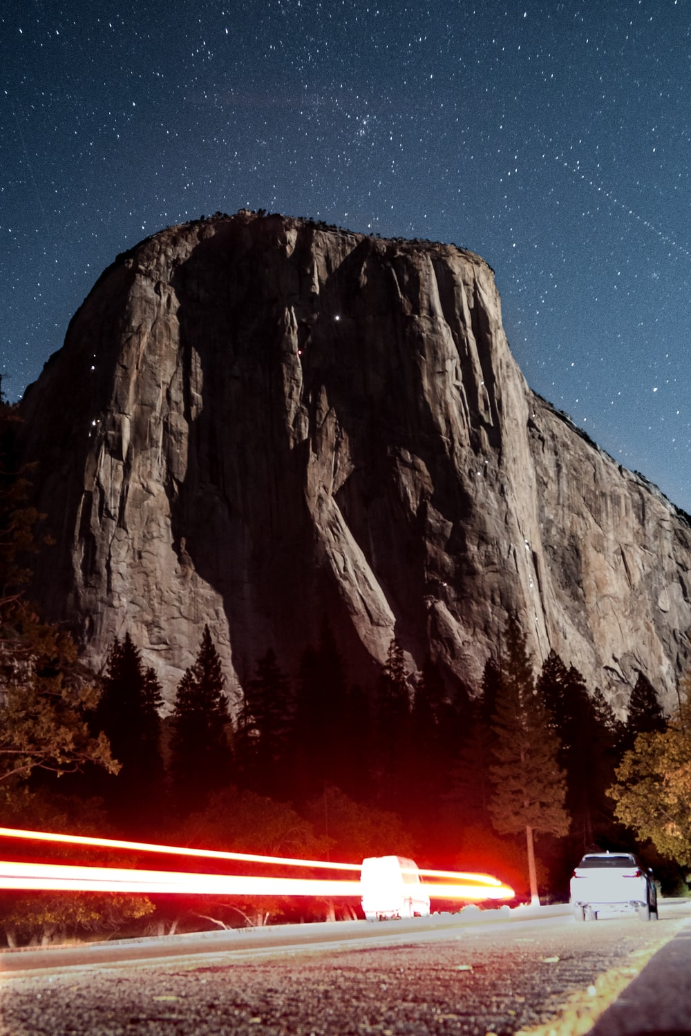 light streak photography of vehicle in the middle of the street near rocky mountain