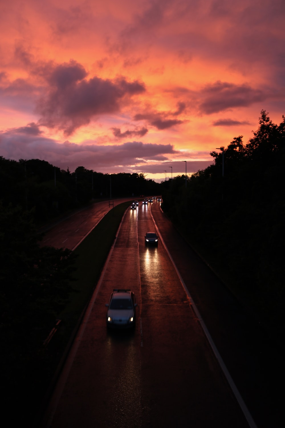 several vehicles on the road during sunset