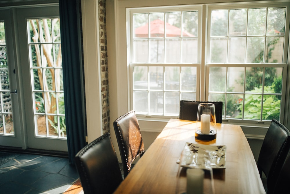 brown wooden dining table and black leather chairs