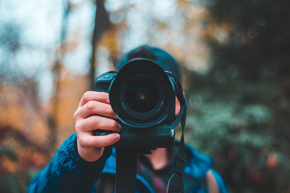 selective focus photography of man holding black DSLR camera