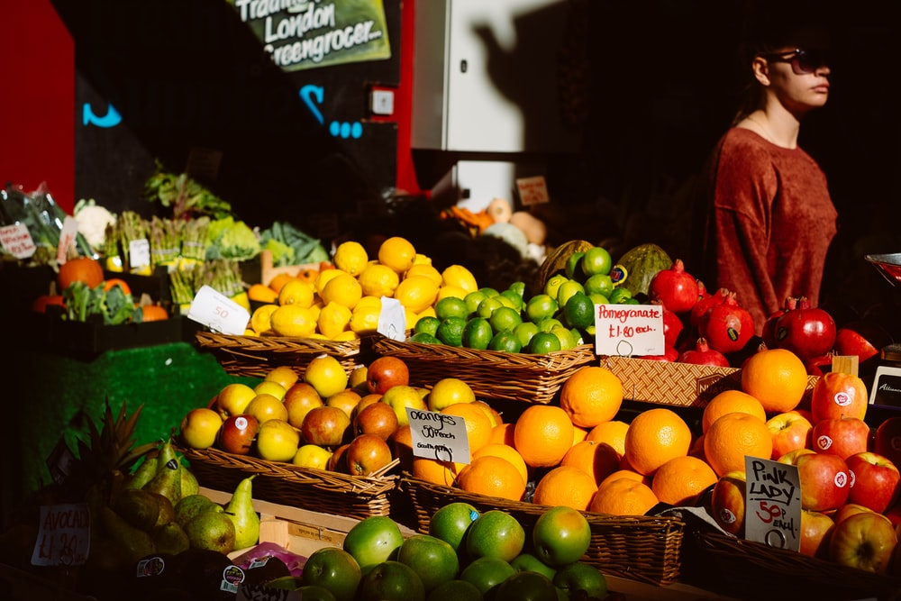 assorted fruits on fruitstand beside woman in brown top