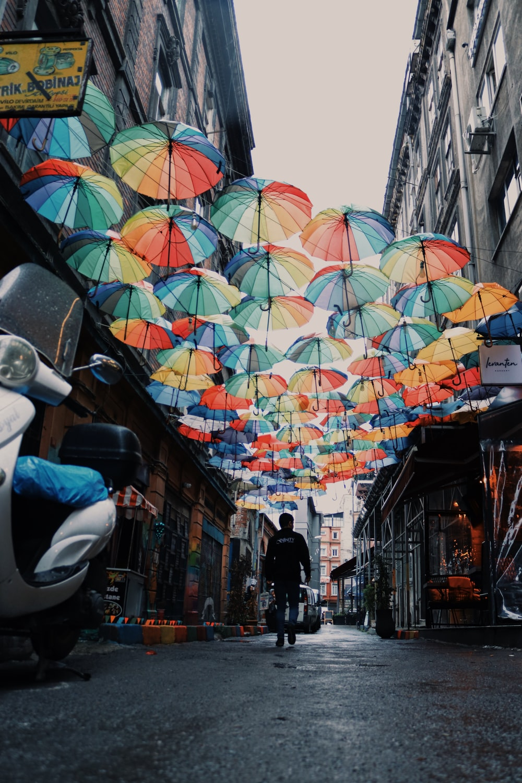 man walking on floating umbrella alley