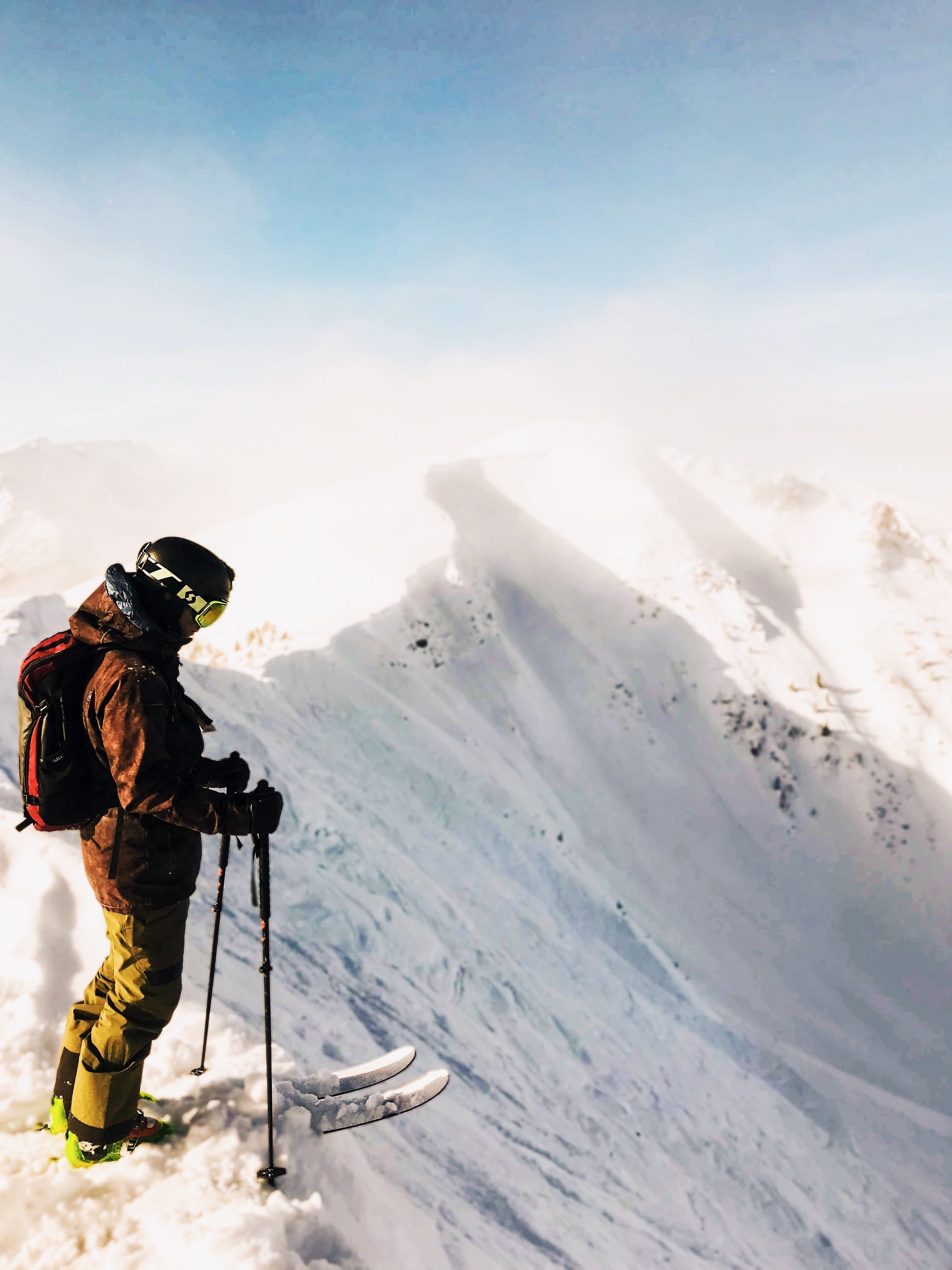man about to ski on top of mountain peak