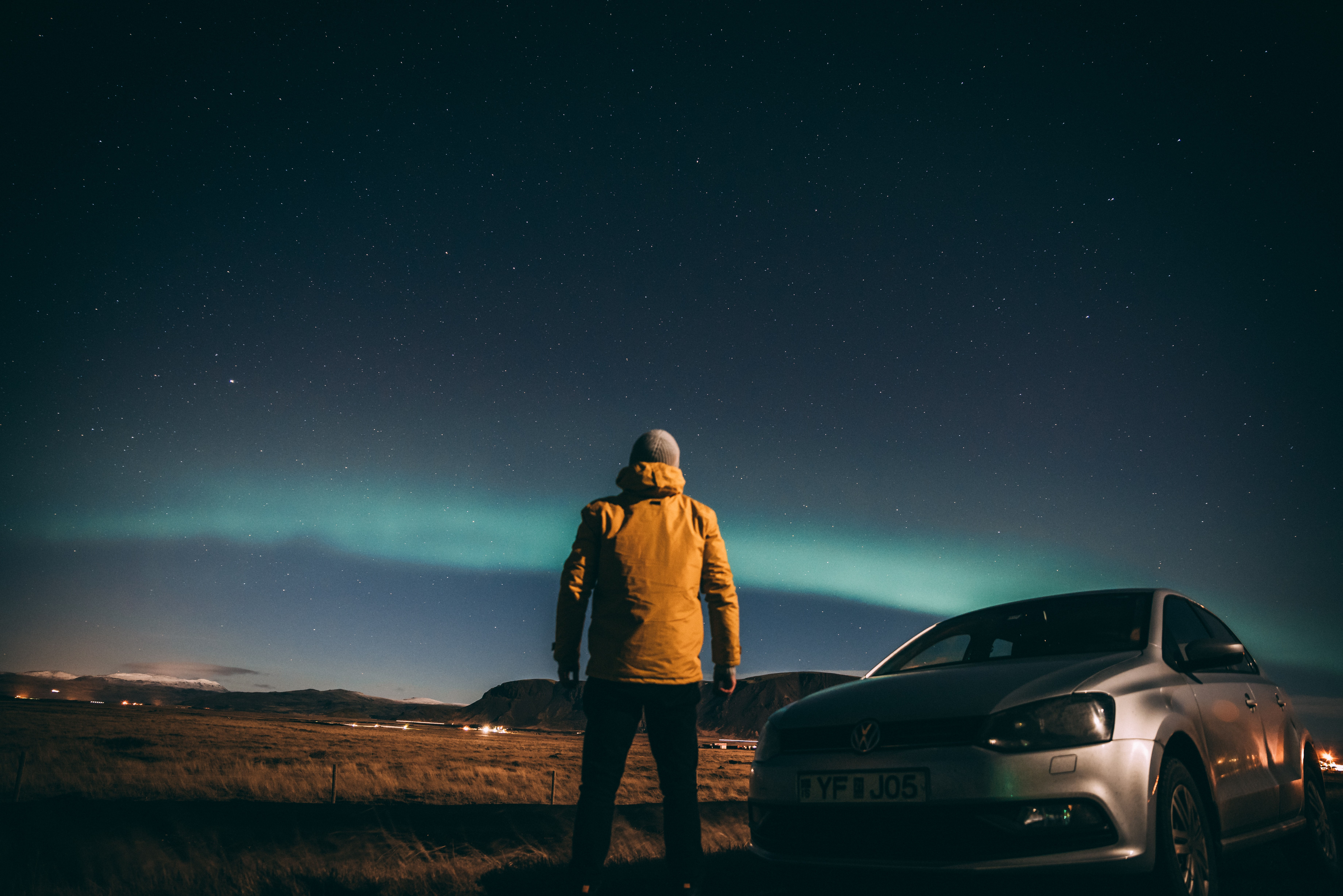 man standing beside gray car while watching Aurora Borealis phenomenon