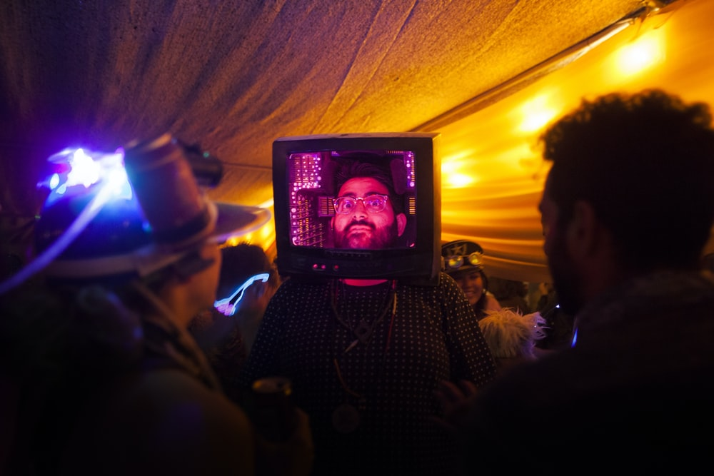 man wearing CRT TV on his head