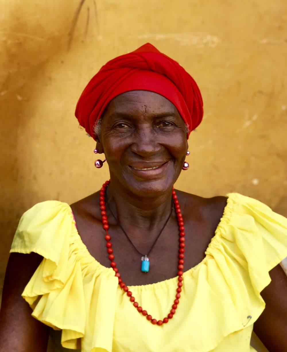 laughing woman wearing beaded necklace and red hat during daytime