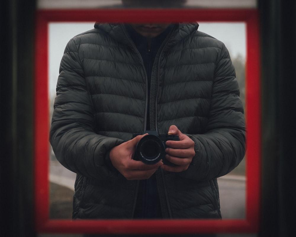 man wearing black bubble jacket holding DSLR camera
