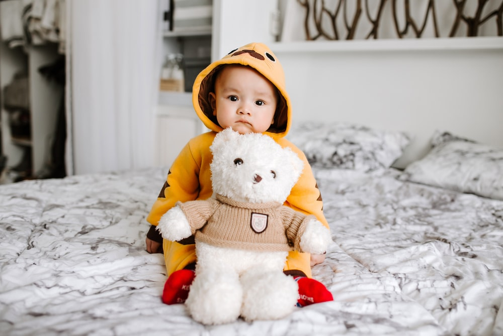 toddler sitting on bed beside white bear plush toy