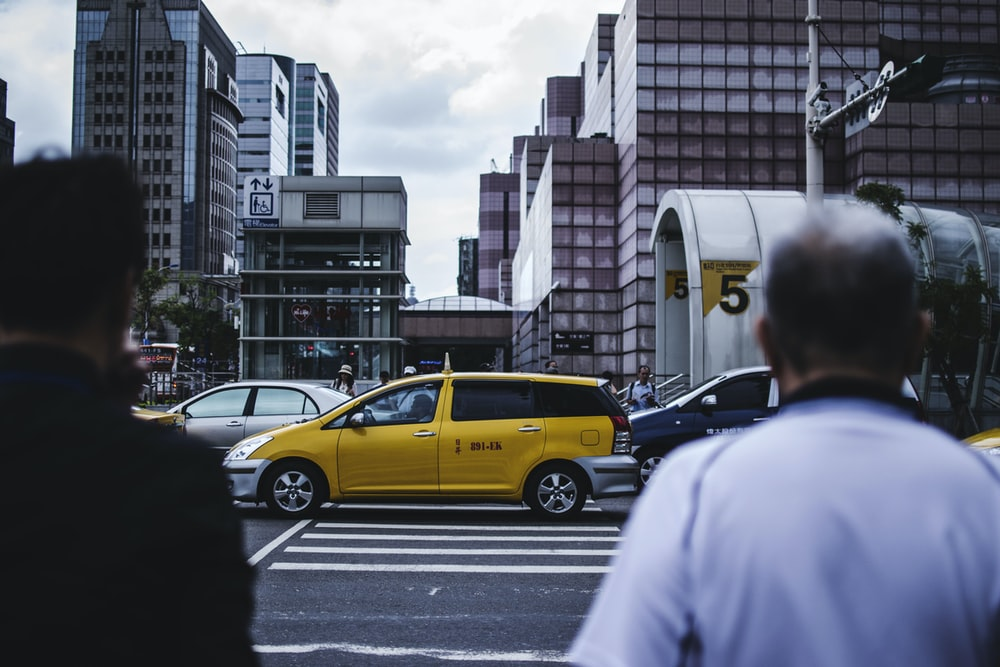 men walking on pedestrian towrds yellow SUV
